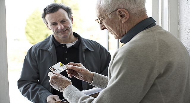 Elderly man inspecting a gas safety register card
