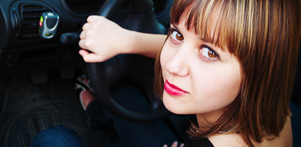 Woman at steering wheel, car insurance for women