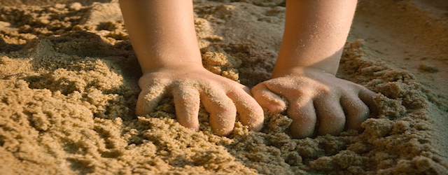 Baby hands in the sand on the beach