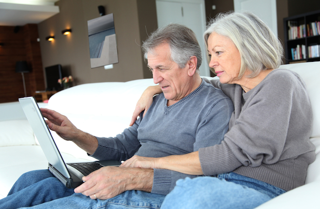 family in their 50s enjoying browsing internet on their laptop